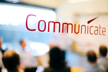 "A screen with the word ""communicate"" in red font"